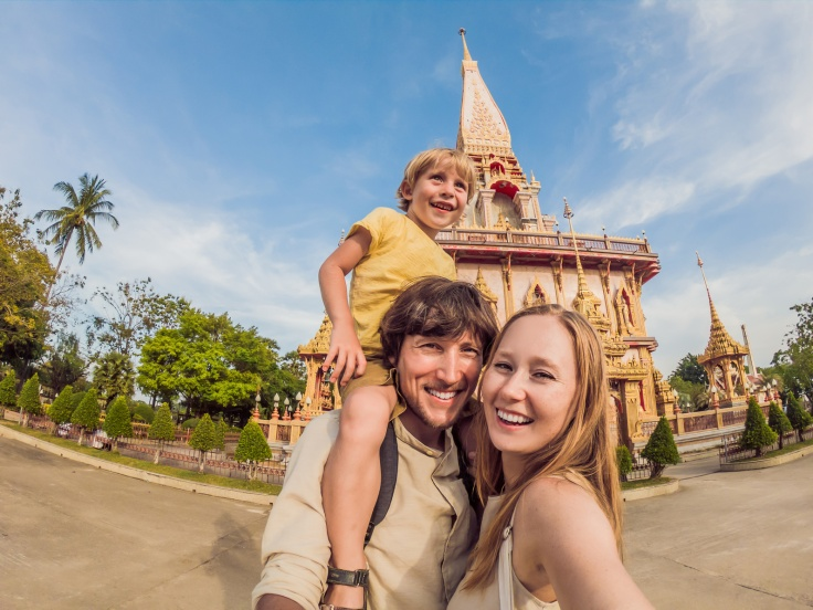 A happy family of tourists on the background of Wat Chalong in Thailand. Traveling with children concept